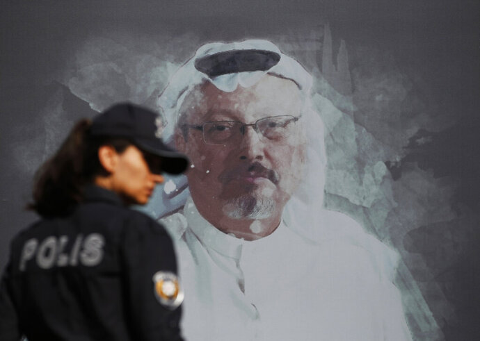 FILE - In this Oct. 2, 2019 file photo, a Turkish police officer walks past a picture of slain Saudi journalist Jamal Khashoggi prior to a ceremony, near the Saudi Arabia consulate in Istanbul, marking the one-year anniversary of his death. A court in Saudi Arabia has sentenced five people to death for the killing of Washington Post columnist Jamal Khashoggi, who was murdered in the Saudi Consulate in Istanbul in October 2018 by a team of Saudi agents. Saudi Arabia's state TV reported Monday, Dec. 23, 2019 that three others were sentenced to prison. All can appeal the verdicts. (AP Photo/Lefteris Pitarakis, File)