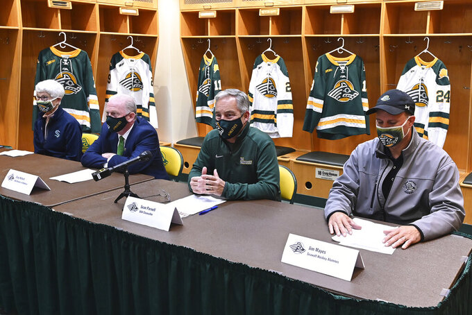 Alaska-Anchorage Chancellor Sean Parnell, second from right, announces the reinstatement of the hockey team at a news conference Tuesday, Aug. 31, 2021, in the hockey locker room in Anchorage, Alaska. From left are Kathie Bethard, Save Seawolf Hockey chairwoman; university athletic director Greg Myford; Parnell; and former hockey player Jim Mayes. Donors, including the NHL's newest team, raised over $3 million after the program was eliminated. (Bill Roth/Anchorage Daily News via AP)
