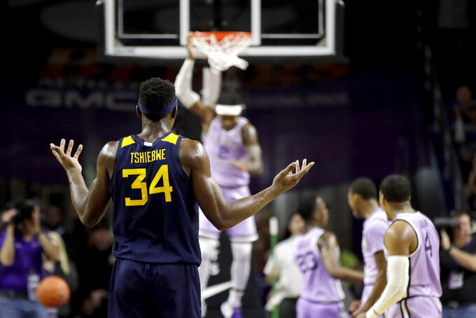 West Virginia's Oscar Tshiebwe (34) reacts after Kansas State's Cartier Diarra dunked the ball during the first half of an NCAA college basketball game Saturday, Jan. 18, 2020, in Lawrence, Kan. (AP Photo/Charlie Riedel)