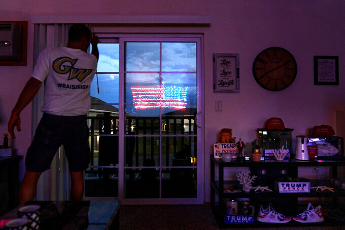 "An illuminated American flag is reflected in the balcony door of Scott Rice's apartment in Appleton, Wis., Aug. 20, 2020. Rice reveres the president the way Wisconsin loves the Green Bay Packers. He has painted ""T-R-U-M-P"" on his lawn, spelled it out with Christmas lights on his roof and painted it on his steel-toed shoes. (AP Photo/David Goldman)"