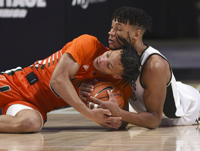 CORRECTS ID TO MIAMI'S ISAIAH WONG, NOT MIAMI'S DONALD CHANEY JR.  - Miami's Isaiah Wong, left, and Wake Forest's Ody Oguama battle for a loose ball in an NCAA college basketball game, Saturday, Jan. 30, 2021, at Joel Coliseum in Winston-Salem, N.C. (Walt Unks/The Winston-Salem Journal via AP)