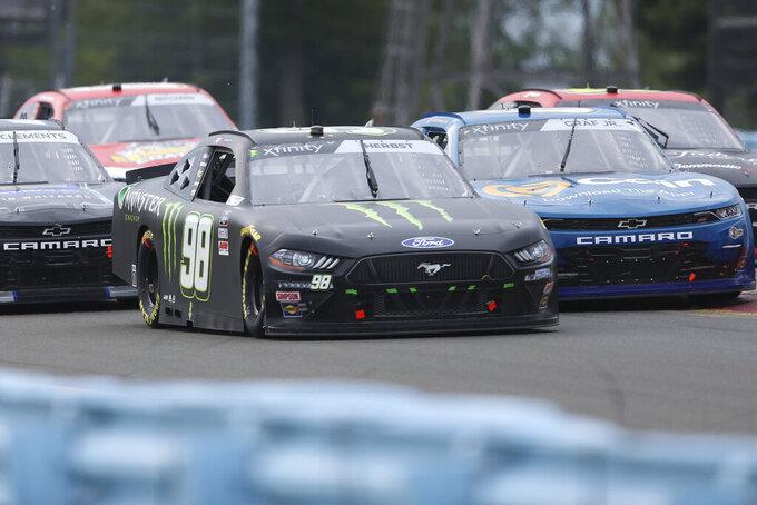 Riley Herbst (98) drives alongside Joe Graf Jr., right, around Turn 1 in the NASCAR Xfinity Series auto race at Watkins Glen International in Watkins Glen, N.Y., on Saturday, Aug. 7, 2021. (AP Photo/Joshua Bessex)