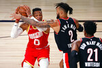 Houston Rockets' Russell Westbrook handles the ball next to Portland Trail Blazers' Gary Trent Jr. (2) during the first half of an NBA basketball game Tuesday, Aug. 4, 2020, in Lake Buena Vista, Fla. (Kevin C. Cox/Pool Photo via AP)