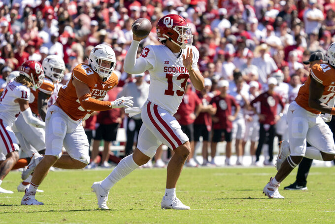 Oklahoma quarterback Caleb Williams (13) looks to pass during the first half of an NCAA college football game against Texas at the Cotton Bowl, Saturday, Oct. 9, 2021, in Dallas. (AP Photo/Jeffrey McWhorter)