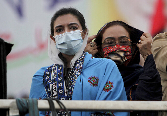 Asifa Bhutto Zardari, left, a leader of the Pakistan Democratic Movement, an alliance of opposition parties, attends an anti-government rally, in Multan, Pakistan, Monday, Nov. 30, 2020. Despite a government ban and arrests of hundreds of activists, Pakistani opposition supporters rallied in a central city on Monday, calling on Prime Minister Imran Khan to resign over alleged bad governance and incompetence. (AP Photo/Asim Tanveer)