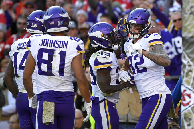 Minnesota Vikings tight end Kyle Rudolph (82) celebrates his touchdown with running back Dalvin Cook (33), wide receiver Bisi Johnson (81) and wide receiver Stefon Diggs (14) during the second half of an NFL football game against the Kansas City Chiefs in Kansas City, Mo., Sunday, Nov. 3, 2019. (AP Photo/Reed Hoffmann)