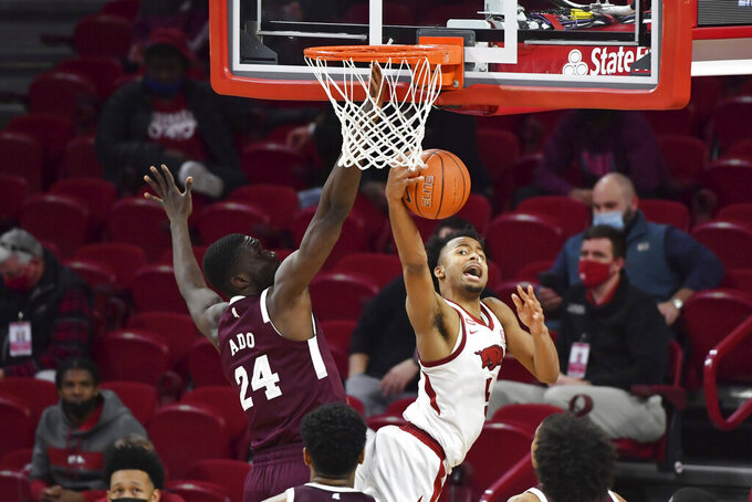 Arkansas guard Moses Moody (5) is defended by Mississippi State's Abdul Ado (24) during the second half of an NCAA college basketball game Tuesday, Feb. 2, 2021, in Fayetteville, Ark. (AP Photo/Michael Woods)