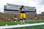 FILE - In this Saturday, Sept. 4, 2021, file photo, Iowa offensive lineman Tyler Linderbaum (65) warms up before an NCAA college football game against Indiana in Iowa City, Iowa. As much as Big Ten teams love having fans back this year after playing without spectators in the pandemic-delayed 2020 season, the change is requiring some adjustments because communicating on the field isn't quite as easy as it was a year ago when they were in empty stadiums.  (AP Photo/Charlie Neibergall, File)