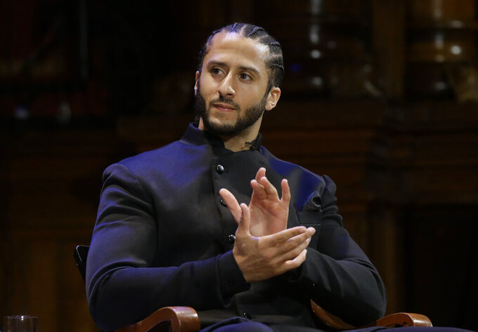 FILE - In this Oct. 11, 2018, file photo, former NFL football quarterback Colin Kaepernick applauds while seated on stage during W.E.B. Du Bois Medal ceremonies at Harvard University in Cambridge, Mass. Republican concerns that the former NFL quarterback is too controversial to honor as a black leader doomed a resolution recognizing Black History Month in the state Assembly, Tuesday, Feb. 12, 2019. The Legislature's black caucus had proposed a resolution honoring a number of black leaders, including Kaepernick, but Assembly Republicans refused to take it up. (AP Photo/Steven Senne, File)