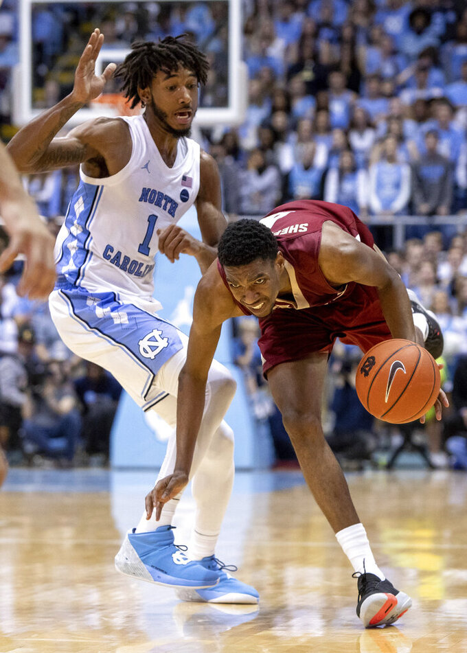 Elon's Marcus Sheffield II, right, stumbles as he dribbles past North Carolina's Leaky Black (1) during the second half of an NCAA college basketball game in Chapel Hill, N.C., Wednesday, Nov. 20, 2019. (AP Photo/Ben McKeown)
