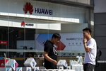 People smoke near a Huawei retail store in Beijing, Tuesday, June 11, 2019. Chinese tech giant Huawei said Tuesday it would have become the world's number one smartphone maker by year's end if it were not for