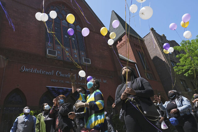 FILE- In this May 21, 2020 file photo, a group of people who could not attend the church service for Bishop Carl Williams, Jr., due to restrictions on the size of gatherings, release balloons to honor his memory in front of his church in the Brooklyn borough of New York. On Friday, June 26, 2020, a federal judge in New York blocked the state from enforcing coronavirus restrictions limiting indoor religious gatherings to 25% capacity when other types of gatherings are limited to 50%. (AP Photo/Seth Wenig)