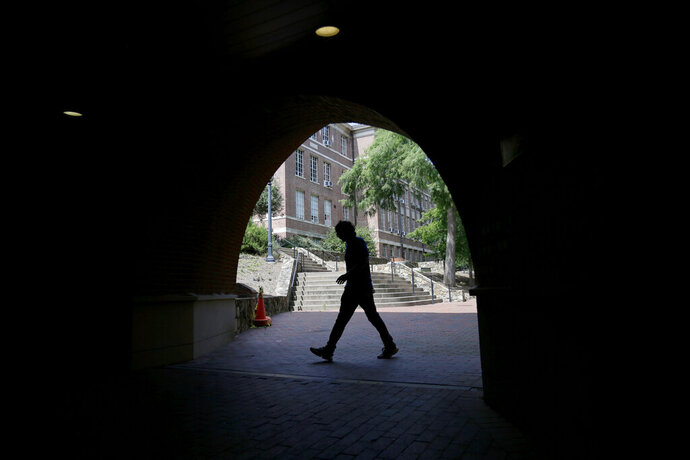 A pedestrian uses a tunnel walkway at the University of North Carolina in Chapel Hill, N.C., Tuesday, June 30, 2020. (AP Photo/Gerry Broome)