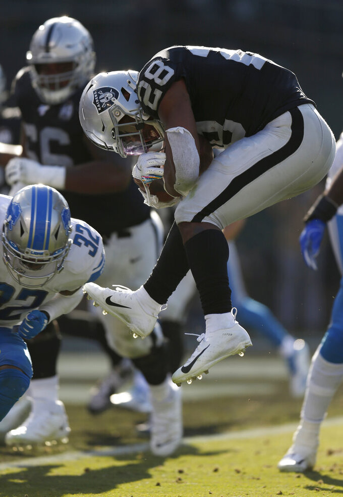 Oakland Raiders running back Josh Jacobs (28) jumps against Detroit Lions defensive back Tavon Wilson (32) before scoring a touchdown during the first half of an NFL football game in Oakland, Calif., Sunday, Nov. 3, 2019. (AP Photo/D. Ross Cameron)