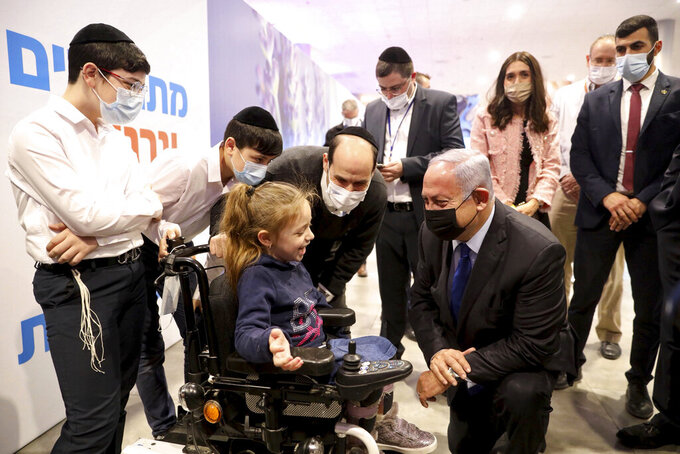 Israeli Prime Minister Benjamin Netanyahu, center right, visits an anti-coronavirus vaccination facility in Jerusalem, Wednesday, Jan. 6, 2021. (Marc Israel Sellem/Pool via AP)