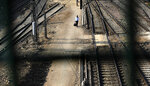 A passenger walks between railway tracks at New Delhi Railway station during a lockdown amid concerns over the spread of Coronavirus, in New Delhi, India, Monday, March 23, 2020. Authorities have gradually started to shutdown much of the country of 1.3 billion people to contain the outbreak. For most people, the new coronavirus causes only mild or moderate symptoms. For some it can cause more severe illness. (AP Photo/Manish Swarup)