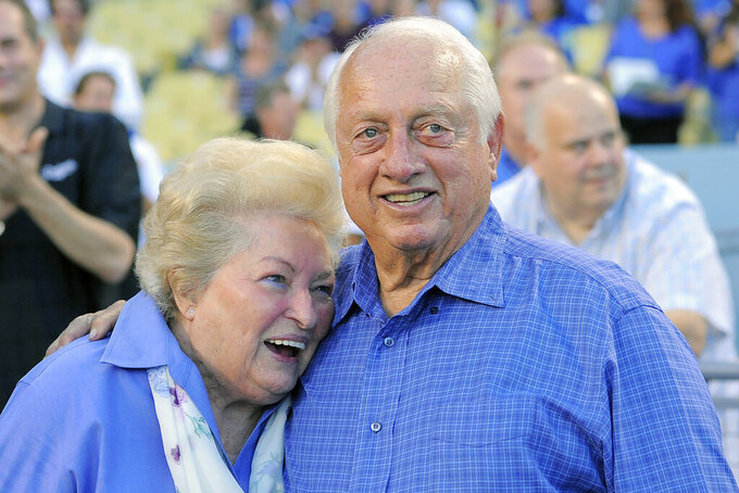 FILE - Tommy Lasorda and his wife Jo hug as they watch a video tribute to Tommy prior to the Los Angeles Dodgers' baseball game against the Colorado Rockies in Los Angeles, in this Saturday, Sept. 28, 2013, file photo. Jo Lasorda has died. She was 91. She died Monday night, Sept. 20, 2021, at her home in Fullerton, the team said Tuesday. No cause of death was given. (AP Photo/Mark J. Terrill)