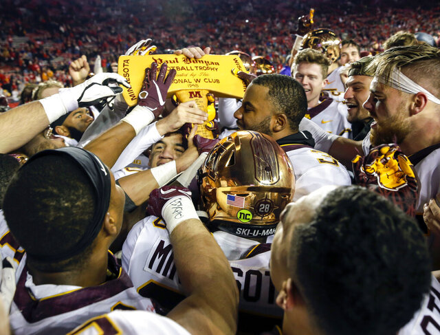 FILE - In this Nov. 24, 2018, file photo, Minnesota players celebrate with the Paul Bunyan Axe trophy after beating Wisconsin 37-15 in an NCAA college football game, in Madison, Wis. More than Paul Bunyan's Axe is on the line in college football's most-played rivalry. The winner of Saturday's game between No. 9 Minnesota and No. 13 Wisconsin wins a division title, and plays No. 2 Ohio State in the Big Ten title game. (AP Photo/Andy Manis, File)