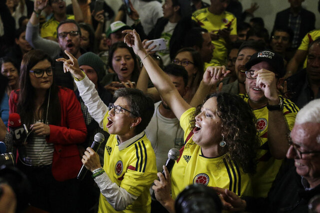 FILE - In this Aug. 26, 2018 file photo, former Senator Claudia Lopez, left, and Senator Angelica Lozano, promoters of a nationwide referendum seeking to curb corruption, address supporters after the polls closed in Bogota, Colombia. Lopez, now Bogota's mayor, announced her nuptial to Angelica Lozano with an enthusiastic message on Twitter late Monday, Dec. 16, 2019, (AP Photo/Ivan Valencia, File)