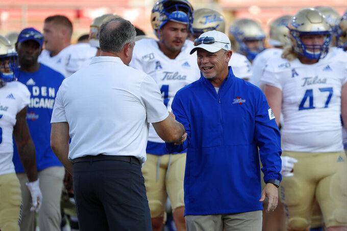 SMU head coach Sonny Dykes, left, meets with Tulsa head coach Philip Montgomery, right, on the field before an NCAA college football game, Saturday, Oct. 5, 2019, in Dallas, Texas. (AP Photo/Roger Steinman)