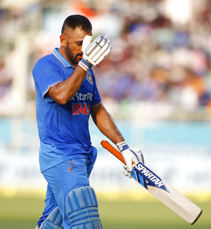 FILE - In this Saturday, Oct. 29, 2016, file photo, Indian cricket captain Mahendra Singh Dhoni leaves the ground after being dismissed during the fifth and last one day international cricket match against New Zealand in Visakhapatnam, India. India great Dhoni announced his retirement from international cricket on Saturday, Aug. 15, 2020. Under Dhoni's stewardship, India won the T20 World Cup in 2007, the 50-over World Cup in 2011 and the Champions Trophy in 2013. (AP Photo/Aijaz Rahi, File)