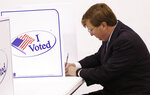 Lt. Gov. Tate Reeves casts his vote at a small voting kiosk in his Flowood, Miss., precinct, Tuesday, Aug. 27, 2019. Reeves is in a runoff for the Republican Party nomination for governor against former Mississippi Supreme Court Chief Justice Bill Waller Jr. (AP Photo/Rogelio V. Solis)