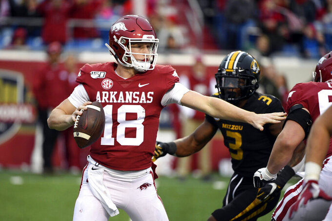 Arkansas quarterback Jack Lindsey tries to get away from Missouri defender Ronnell Perkins during the second half of an NCAA college football game, Friday, Nov. 29, 2019, in Little Rock, Ark. (AP Photo/Michael Woods)