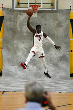 Miami Heat's Victor Oladipo jumps as he poses for a photographer during the NBA basketball team's Media Day in Miami, Monday, Sept. 27, 2021. (AP Photo/Rebecca Blackwell)
