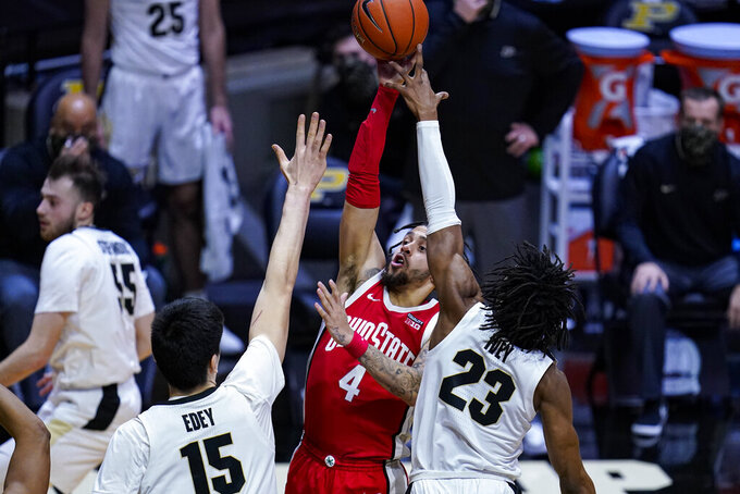 Ohio State guard Duane Washington Jr. (4) shoots between Purdue center Zach Edey (15) and guard Jaden Ivey (23) during the first half of an NCAA college basketball game in West Lafayette, Ind., Wednesday, Dec. 16, 2020. (AP Photo/Michael Conroy)