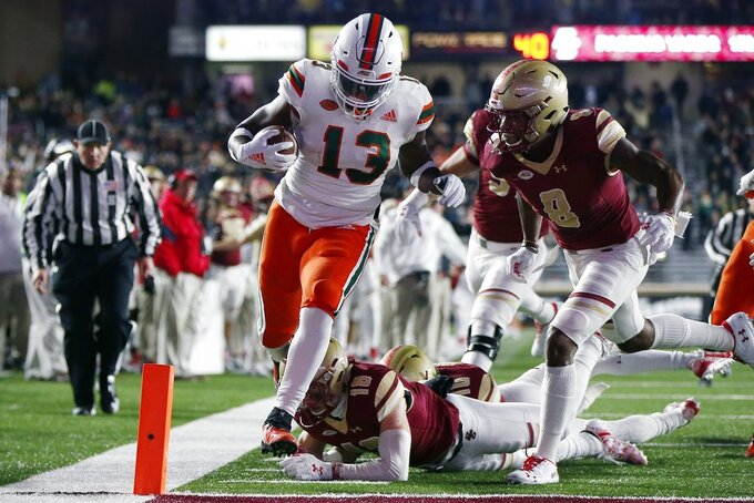 Miami running back DeeJay Dallas (13) scores against Boston College defensive back Mike Palmer (18) and defensive back Will Harris (8) during the first half of an NCAA college football game in Boston, Friday, Oct. 26, 2018. (AP Photo/Michael Dwyer)