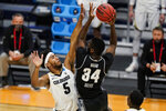 Georgetown center Qudus Wahab (34) shoots over Colorado guard D'Shawn Schwartz (5) in the first half of a first-round game in the NCAA men's college basketball tournament at Hinkle Fieldhouse in Indianapolis, Saturday, March 20, 2021. (AP Photo/Michael Conroy)