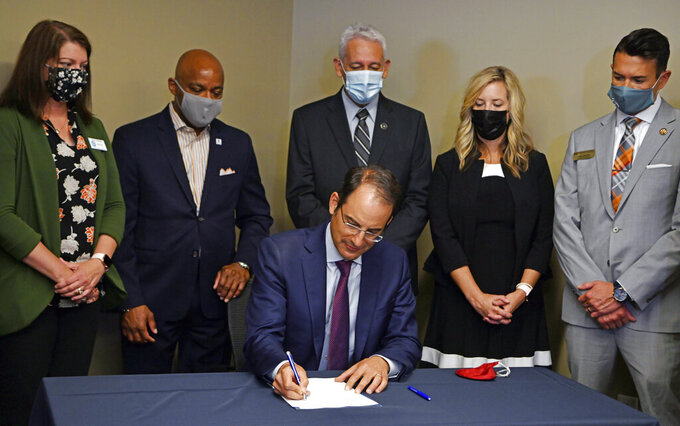 Colorado Attorney General Phil Weiser signs a memorandum of understanding following a press conference announcing the statewide allocation of settlement dollars from major opioid companies at the Ralph L. Carr Colorado Judicial Center on Thursday, Aug. 26, 2021 in Denver. (Eric Lutzens/The Denver Post via AP)