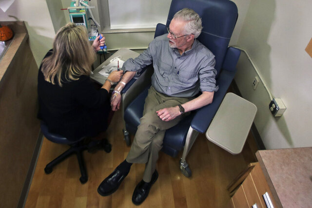 Charles Flagg, who is stricken with Alzheimer's disease, sits for an infusion while participating in a study on the drug Aducanumab at Butler Hospital in Providence, R.I. New results were released on the experimental medicine whose maker claims it can slow the decline of Alzheimer's disease, the most common form of dementia. (AP Photo/Charles Krupa)