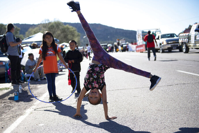 In this Sept. 8, 2018 image, Tomica Johnson, 8, of Fort Defiance, Arizona, does cartwheels during the Navajo Nation Fair Parade near Tse Bonito, New Mexico. (Alma E. Hernandez/Gallup Independent via AP)