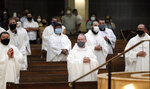 In this photo taken Saturday, June 20, 2020, priests from the Rio Grande Valley wear face masks against the spread of the coronavirus as they attend a Priestly Ordination Ceremony at the Basilica of Our Lady of San Juan Del Valle in San Juan, Texas. (Delcia Lopez/The Monitor via AP)