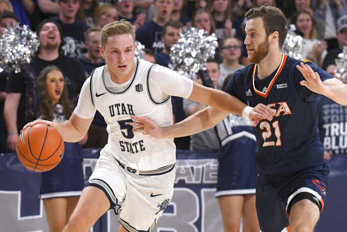 Utah State guard Sam Merrill (5) dribbles the ball as UTSA guard Knox Hellums (21) defends during the first half of an NCAA college basketball game Monday, Nov. 18, 2019, in Logan, Utah. (AP Photo/Eli Lucero)