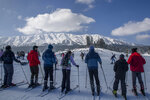 """Tourists wait for their turn to use ski-lift used to transport them up a slope top in Gulmarg, northwest of Srinagar, Indian controlled Kashmir, Sunday, Jan. 10, 2021. Snow this winter has brought along with it thousands of locals and tourists to Indian-controlled Kashmir's high plateau, pastoral Gulmarg, which translates as """"meadow of flowers."""