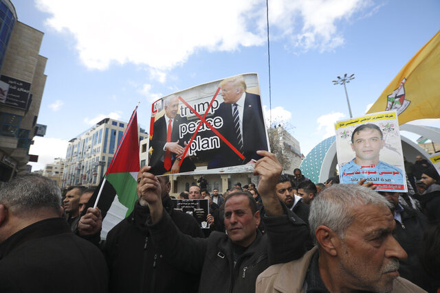 Palestinians protest the Mideast plan announced by the U.S. President Donald Trump, in Hebron, West Bank, Thursday, Jan. 30, 2020. Trump's Mideast plan would create a disjointed Palestinian state with a capital on the outskirts of east Jerusalem, beyond the separation barrier built by Israel. The rest of the Jerusalem, including the Old City, would remain Israel's capital. (AP Photo/Mahmoud Illean)