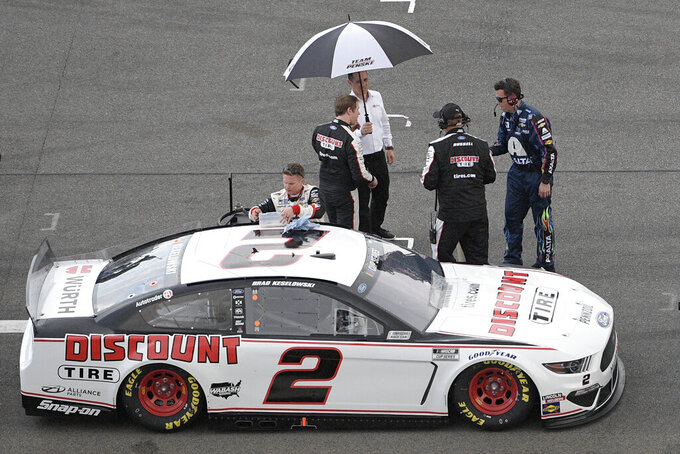 Brad Keselowski stands under an umbrella on pit road as rain forces a red flag during the NASCAR Daytona 500 auto race at Daytona International Speedway, Sunday, Feb. 16, 2020, in Daytona Beach, Fla. (AP Photo/Phelan M. Ebenhack)