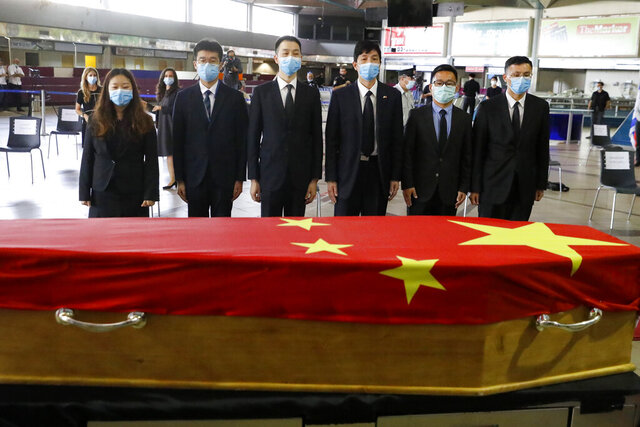 Chinese officials pay their respect in front of the flag-draped coffin of Ambassador Du Wei, who died at his home in the coastal city of Herzliya, during a ceremony at Ben-Gurion International Airport, near Tel Aviv, Wednesday, May 20, 2020. China sent a team to Israel to repatriate the body of its ambassador. (Photo by Jack Guez/Pool via AP)