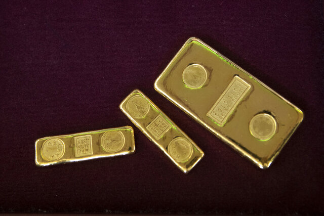 FILE - In this April 16, 2020, file photo, a customer puts gold bars on basket for sell to a gold shop in Bangkok, Thailand. The price of gold surged more than $30 on Monday, July 27, 2020 to over $1,926 per ounce as investors step up buying of the precious metal often sought in times of uncertainty. Gold was trading at $1,926.20 by early afternoon in Asia, up 1.5%, after surging over the weekend. (AP Photo/Sakchai Lalit, File)