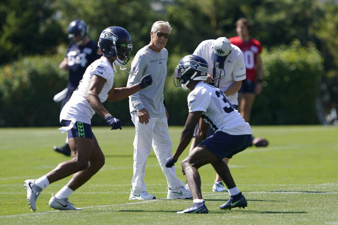 Seattle Seahawks head coach Pete Carroll, center, watches as cornerback Ahkello Witherspoon, left, runs a drill with cornerback Bryan Mills, right, during NFL football practice Thursday, July 29, 2021, in Renton, Wash. (AP Photo/Ted S. Warren)