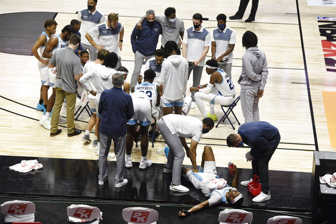 Rhode Island's Antwan Walker, bottom right, is tended to as his team huddles during a timeout in the second half of an NCAA college basketball game against Arizona State, Wednesday, Nov. 25, 2020, in Uncasville, Conn. (AP Photo/Jessica Hill)