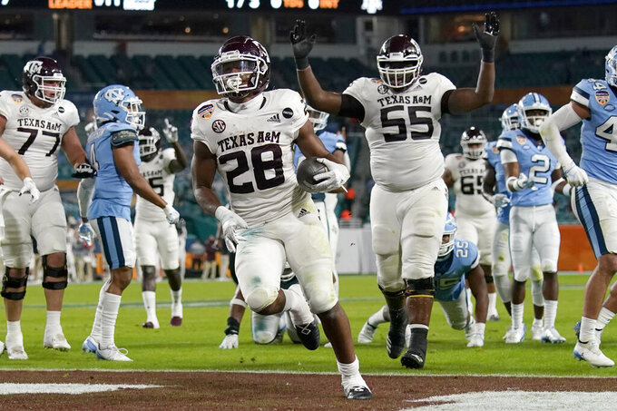 Texas A&M running back Isaiah Spiller (28) runs to score a touchdown during the first half of the Orange Bowl NCAA college football game against North Carolina, Saturday, Jan. 2, 2021, in Miami Gardens, Fla.(AP Photo/Lynne Sladky)