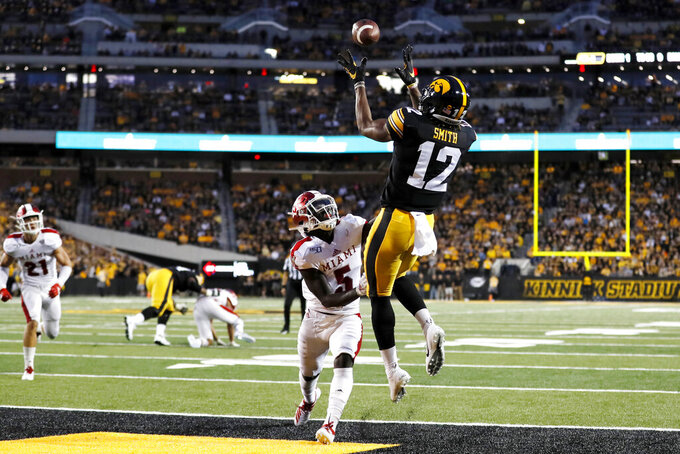 Iowa wide receiver Brandon Smith (12) catches a touchdown pass over Miami of Ohio defensive back Emmanuel Rugamba (5) during the first half of an NCAA college football game, Saturday, Aug. 31, 2019, in Iowa City, Iowa. (AP Photo/Charlie Neibergall)