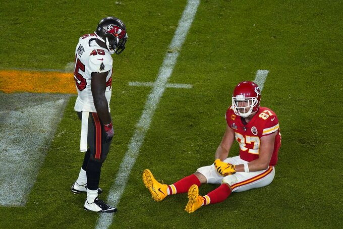Kansas City Chiefs' Travis Kelce (87) sits on the ground in front of Tampa Bay Buccaneers' Devin White (45) during the second half of the NFL Super Bowl 55 football game Sunday, Feb. 7, 2021, in Tampa, Fla. (AP Photo/Charlie Riedel)
