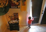 Athena Chavez, 2, the daughter of Aaron Francisco Chavez, looks out a nearby door as she stands next to a shrine for Aaron at the family home Wednesday, Feb. 6, 2019, in Tucson, Ariz. Aaron Chavez died of a fentanyl overdose at the age of 19. (AP Photo/Ross D. Franklin)
