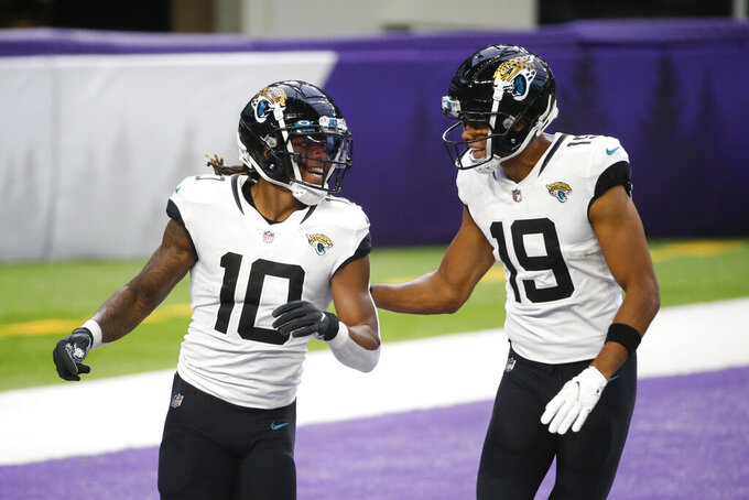 Jacksonville Jaguars wide receiver Laviska Shenault Jr. celebrates with teammate Collin Johnson., right, after catching a 28-yard touchdown pass during the first half of an NFL football game against the Minnesota Vikings, Sunday, Dec. 6, 2020, in Minneapolis. (AP Photo/Bruce Kluckhohn)