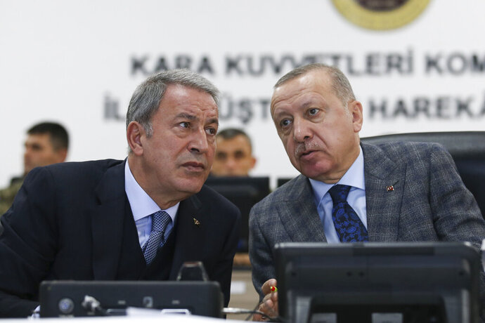 Turkish President Recep Tayyip Erdogan, right, speaks with Defence Minister Hulusi Akar as they visit a military coordination center set up for Turkey's Syria operation, in Sanliurfa, southeastern Turkey, Sunday, Nov. 3, 2019. (Presidential Press Service via AP, Pool)