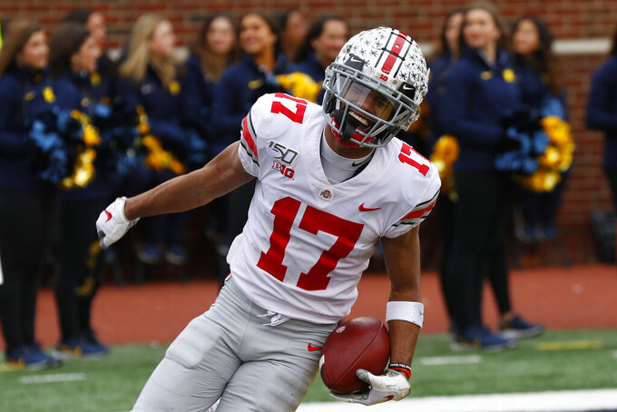 FILE - Ohio State wide receiver Chris Olave (17) celebrates catching a 57-yard touchdown pass against Michigan in the first half of an NCAA college football game in Ann Arbor, Mich., in this Saturday, Nov. 30, 2019, file photo. Olave was selected to The Associated Press Preseason All-America first team offense, Monday Aug. 23, 2021. (AP Photo/Paul Sancya, File)